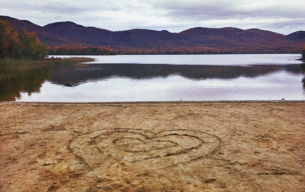A hopeful image, with a view of Vermont mountains with a system of hearts drawn in the sand by hand.