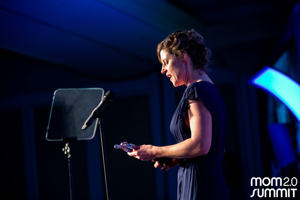 Standing at the mic under spotlights with goosebumps on my arms at Mom2 Summit accepting an award for sponsored writing