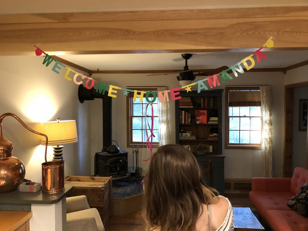 A welcome home banner and my daughter after a writing conference