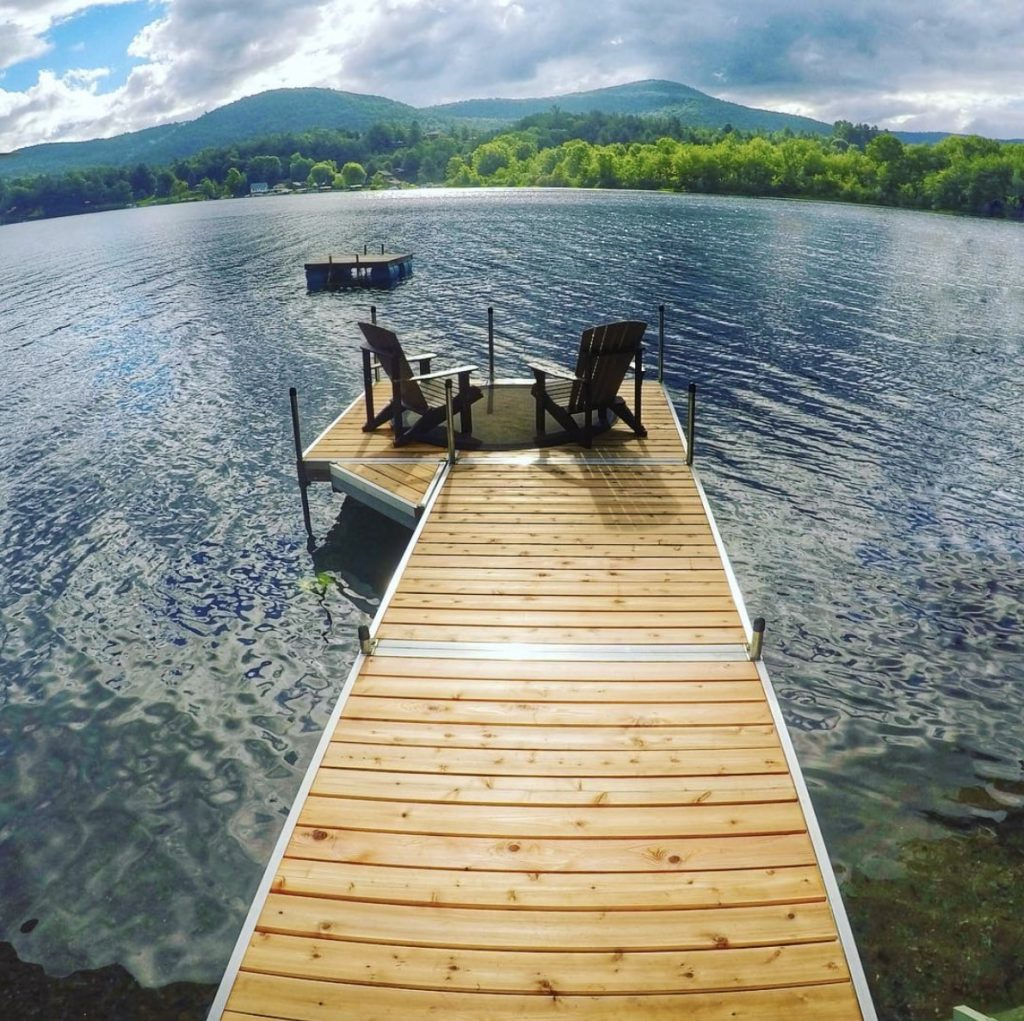 A cedar dock with two Adirondack chairs.