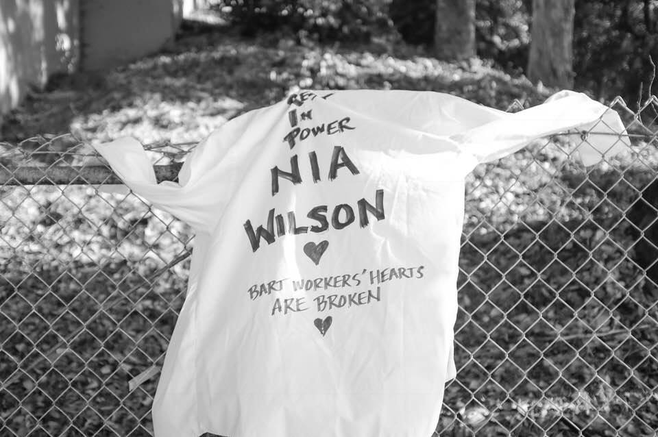 A shirt draped on a fence with the writing: rest in power Nia. The workers of BART are heartbroken