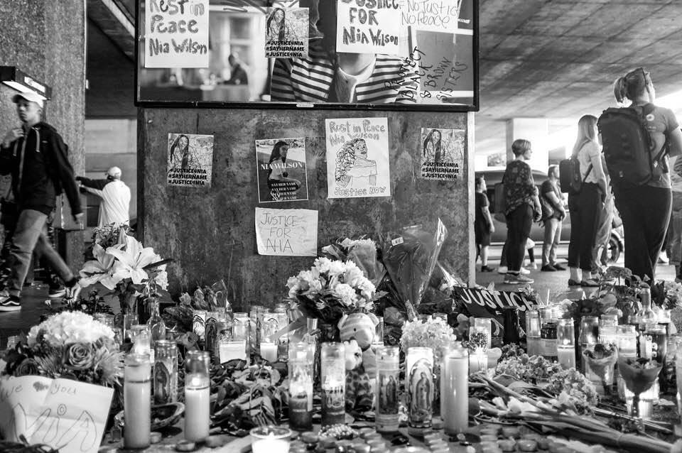 Black and white photo of flowers left for Nia Wilson at MacArthur Station