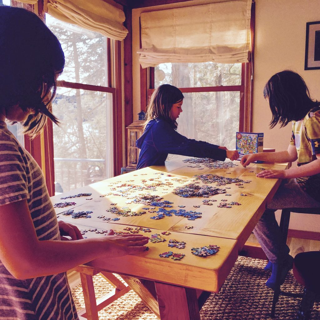 Three girls work on a puzzle in afternoon light.