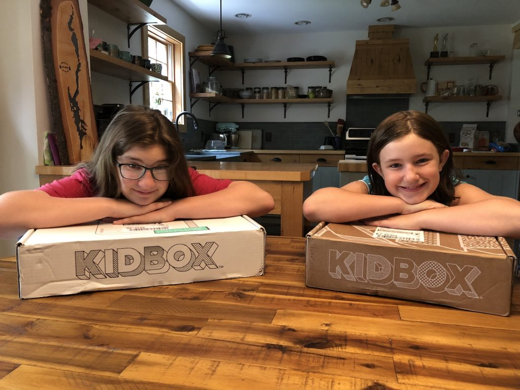 Two girls rest their heads on Kidbox boxes.