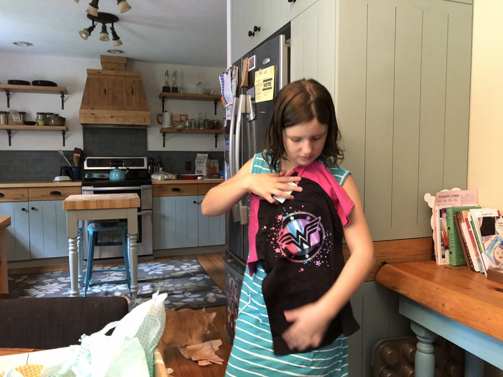 Young girl holds a superhero shirt.