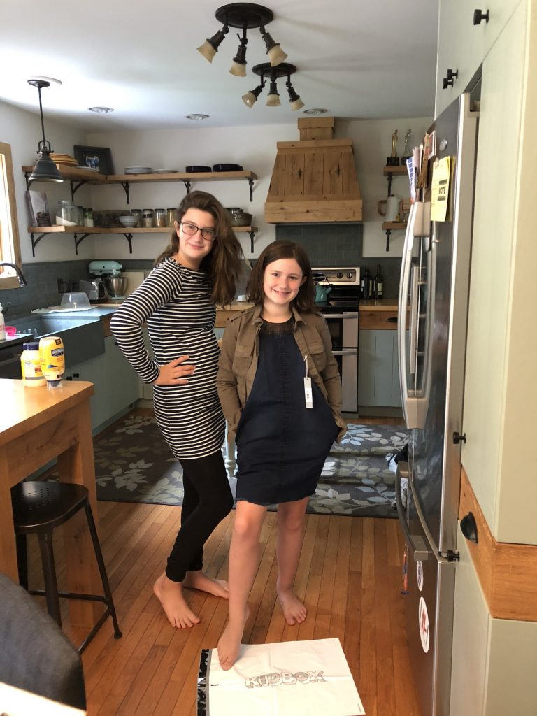 Two sisters stand fashionably modeling fall clothing.