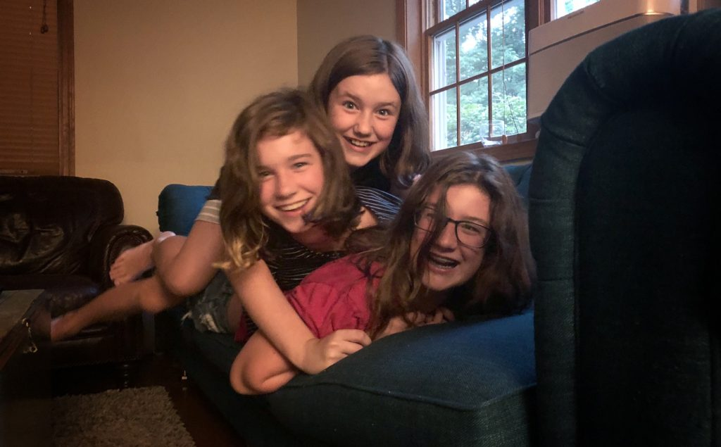 Three sisters piled on top of each other and laughing on a couch.