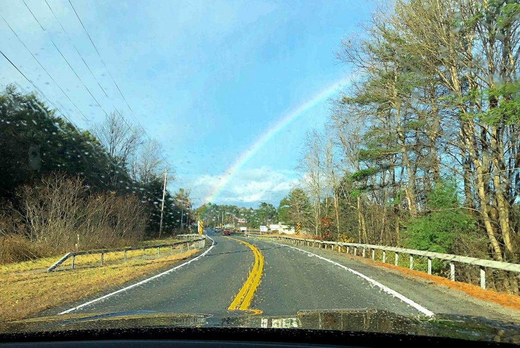 A rainbow across a blue sky seen through the rainy windshield of a black car.