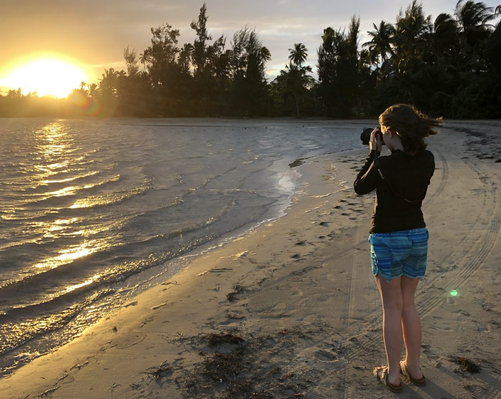 A young girl stands on the beach at sunrise, she holds a camera to her face and faces the water.