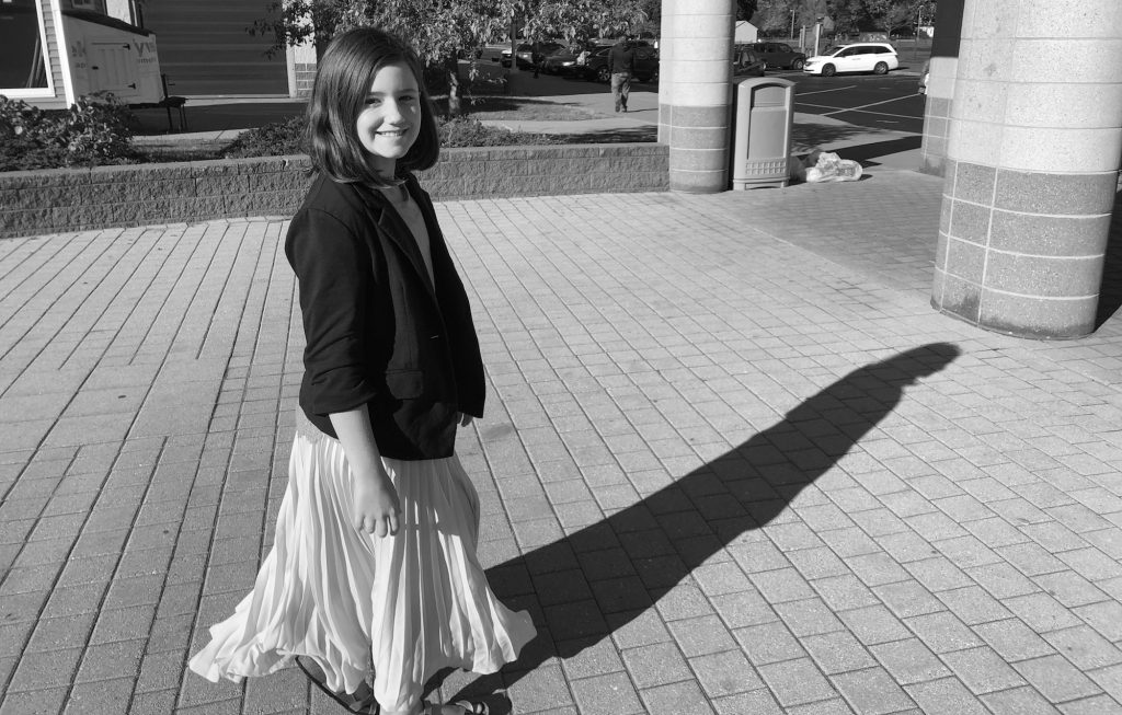A ten year old girl smiles at the camera as she walks. She has a long pleated skirt on and she casts a shadow. The photo is black and white.