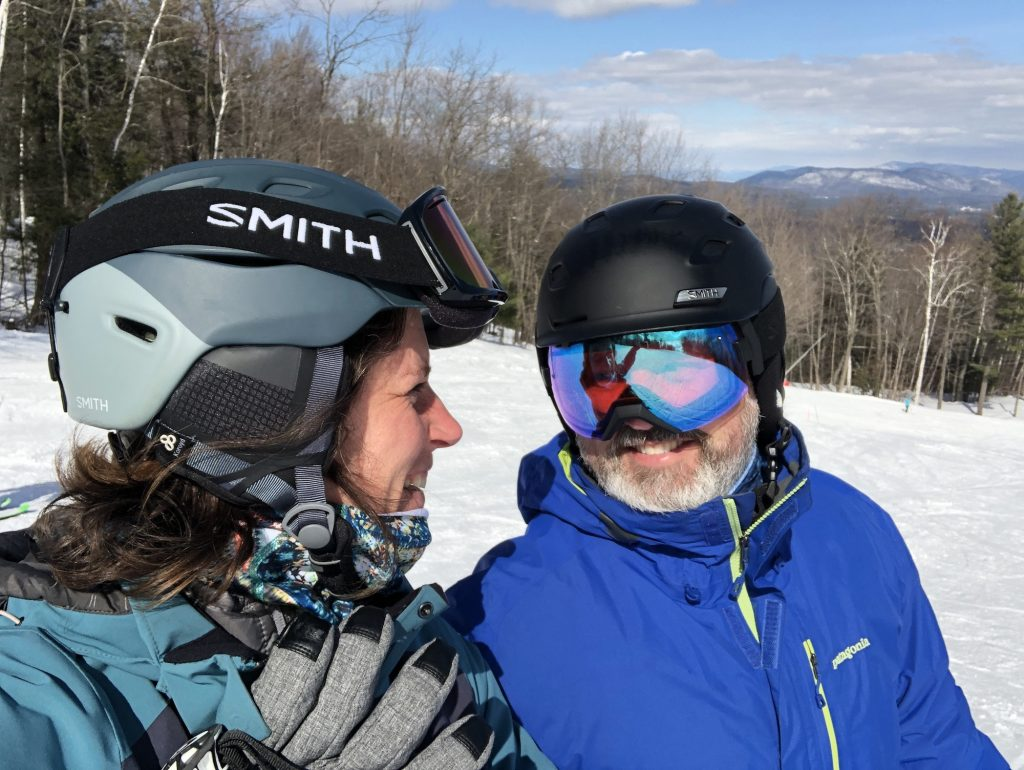 A man and woman in ski gear smile at each other.