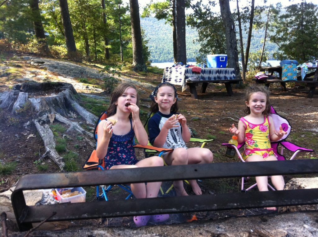 Three young girls sit on camp chairs eating s'mores at a campsite with pine trees and a view of the lake in the background.