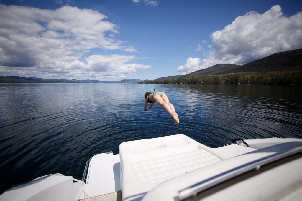 A woman wearing a bikini dives off the bat of a boat into a lake. The sky is blue with a few puffy clouds and to the right of the frame is a mountain.