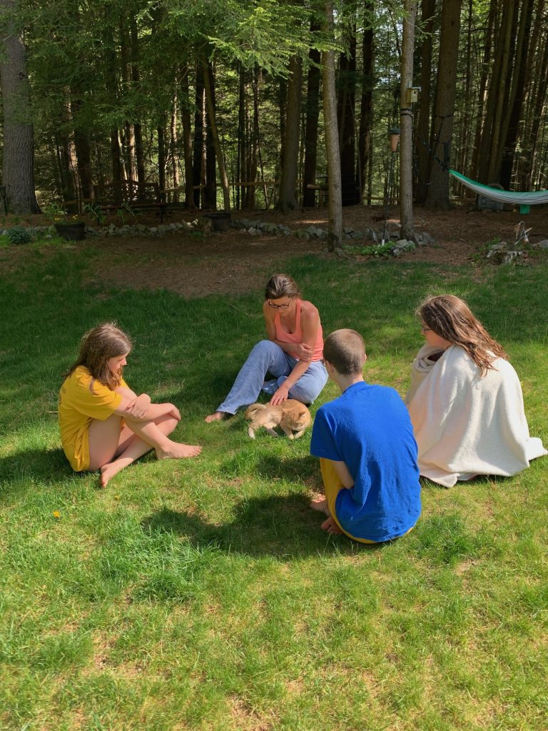 A woman and three teenage girls sit in a circle around a sick tabby cat.