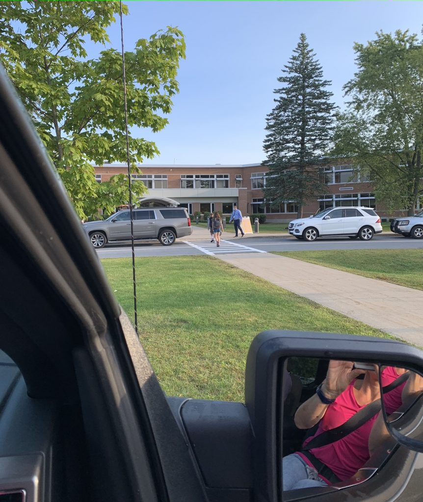 A student walks across a school crosswalk, a woman's reflection is shown in the side mirror of a truck, she is taking a photo of the student.